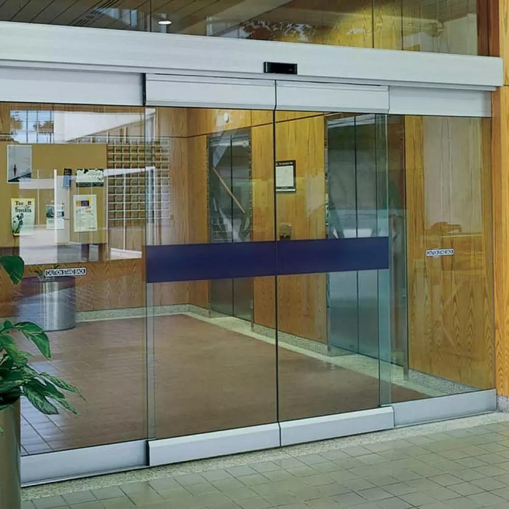 Foyer yang menarik, lingkungan belanja yang mengundang, pengaturan meja yang megah; ada kalanya Anda ingin memamerkan pemandangan spektakuler tanpa halangan. ASSA ABLOY Sistem pintu geser serba kaca menghadirkan solusi ramping dan bergaya yang nyaman dilihat dan sangat fungsional.  Hadir dalam dua varian; transparan (ASSA ABLOY SL500 T) dan semi-transparan dengan rel (ASSA ABLOY SL500 R); keduanya ideal sebagai pintu masuk internal atau sekunder di mana permintaan akan estetika kelas tinggi melebihi kebutuhan akan ketahanan. Profil aluminium anodized bening mendukung daun pintu kaca tak terputus yang meluncur membuka dan menutup dengan tenang; tampaknya tanpa dukungan bingkai apa pun.  Transparan hanya memiliki profil aluminium atas dan sangat ideal untuk aplikasi internal. Muncul dalam berbagai macam pengaturan, dengan banyak tambahan opsional, menawarkan Anda kemampuan untuk menyesuaikan spesifikasi dengan kebutuhan Anda.  Semi-transparan menggunakan kaca yang diperkuat sebagai standar, dengan rel atas dan bawah sebagai penopang. Profil tambahan membuat pengaturan ini lebih cocok untuk aplikasi eksternal daripada Transparan.